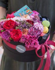 Композиция с цветами и макарунами в низкой черной шляпной коробке